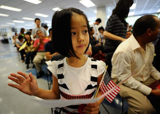 Young girl holding flag at naturalization ceremony