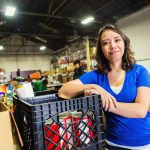Young woman volunteering in food bank warehouse