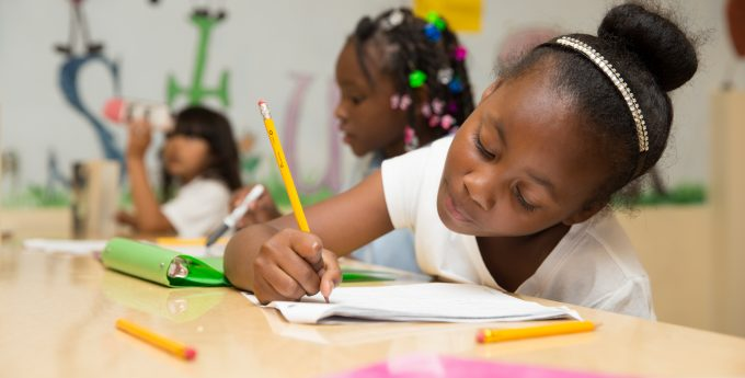 Children writing in the classroom