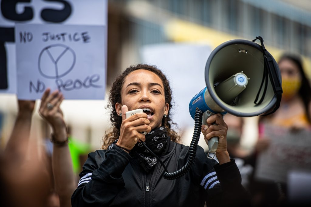 Young Black woman with megaphone at rally