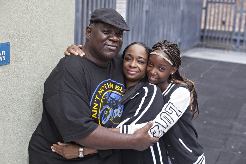 Three individuals embrace each other