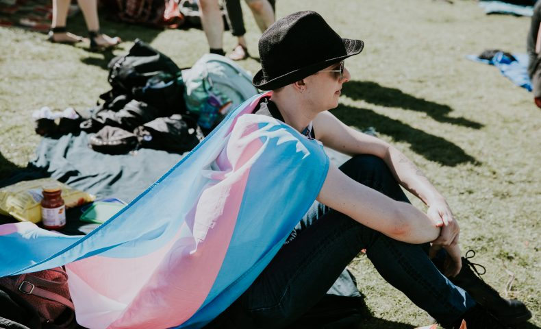 Person sitting on grass with trans flag
