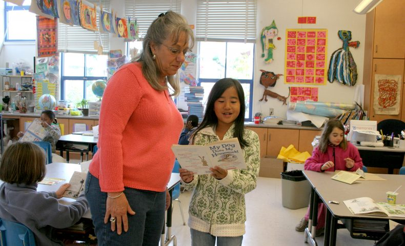 Young student reading to teacher in classroom