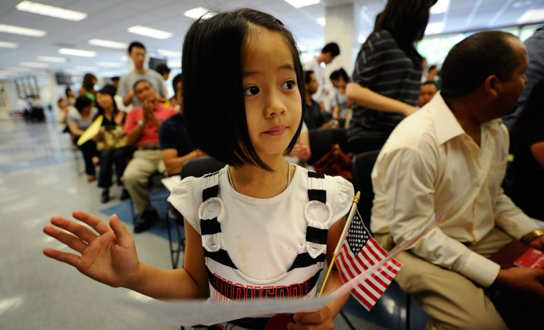 Young girl at citizenship ceremony holding flag