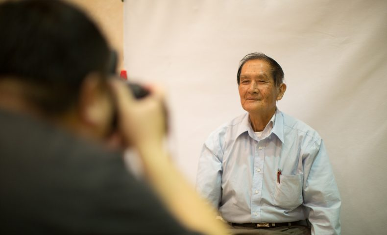 Elderly man getting his photo taken at naturalization fair