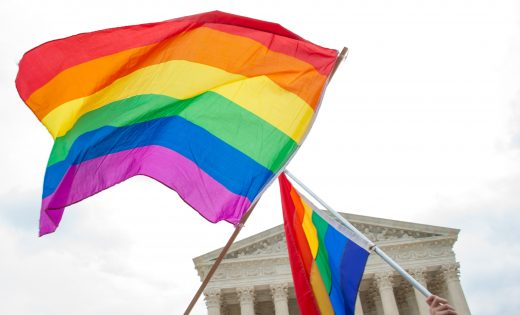Two rainbow flags fly across the Supreme Court of the United States of America