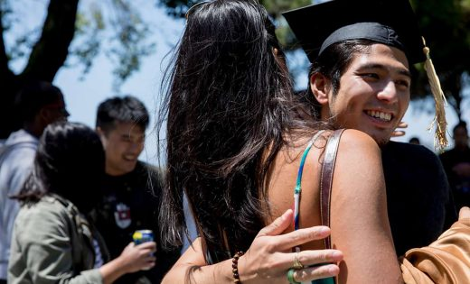 "Jirayut ""New"" Latthivongskorn hugs a high school friend while wearing his mortarboard during his graduation party at Marina Park in San Leandro to celebrate his achievement at UCSF's School of Medicine."