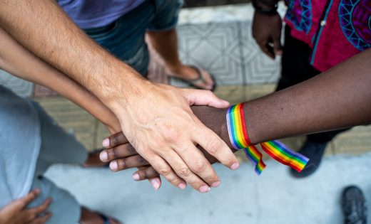 Hands in the center with rainbow bracelet