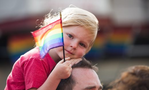 All Children Matter. young girl riding dad's shoulder holding rainbow flag
