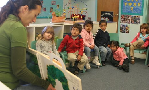 Preschool teacher reading to kids in classroom