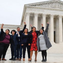 Five students stand in front of SCOTUS with their fist in the air