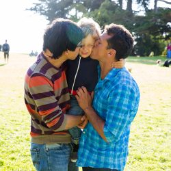 Two fathers embrace their son on a green lawn
