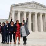 Five students in front of SCOTUS with fist in the air