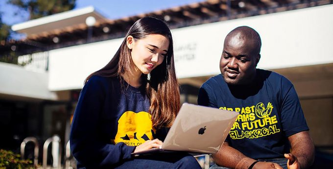 Two students at University of California, Berkeley looking at a laptop together.