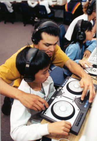 Student with teacher in computer and music lab
